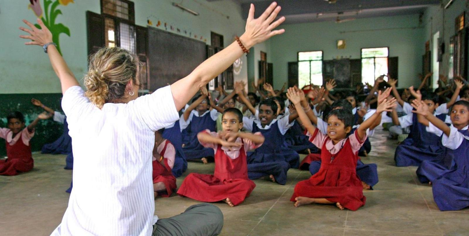 Teaching volunteer plays a game with her primary school students during English class in India.